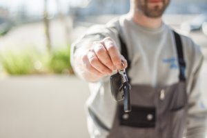 a person handing over a car key